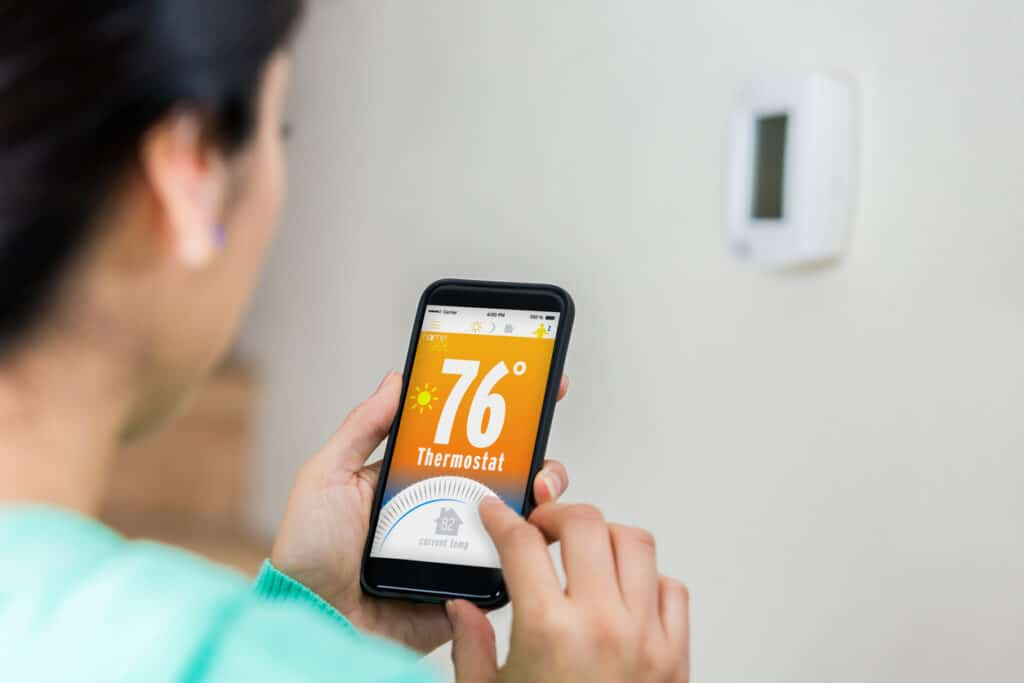 Woman uses smart phone to control thermostat